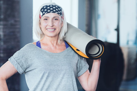 Feeling much healthier. Full of joy retired woman Standing with a mat oh her shoulder and grinning broadly into the camera at a fitness club. Stock Photo