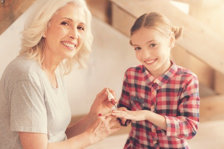 Joyful positive nice woman smiling and painting nails of her granddaughter while wanting her to look beautiful Stock Photo