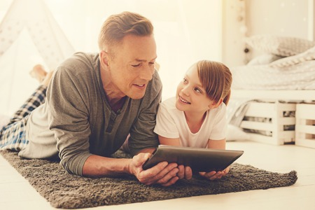 Joyful positive delighted father and daughter lying on the floor and using a tablet while spending time together