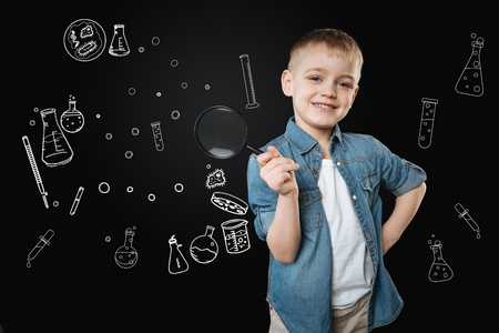 Optimistic clever little boy feeling interested and smiling while being at the exciting lesson and standing with a magnifying glass in his hand