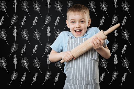 Cheerful enthusiastic little boy feeling excited while standing with a trolling pin and feeling ready to start cooking