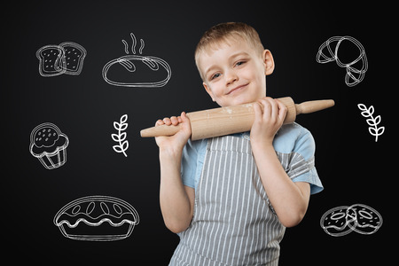 Positive enthusiastic little boy smiling and holding a big wooden rolling pin while learning to bake cakes