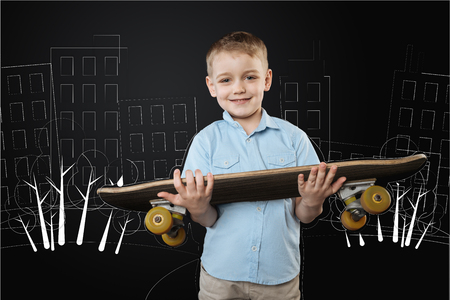 Cheerful active little boy smiling and holding a big convenient skateboard while coming to the yard to play with his best friend