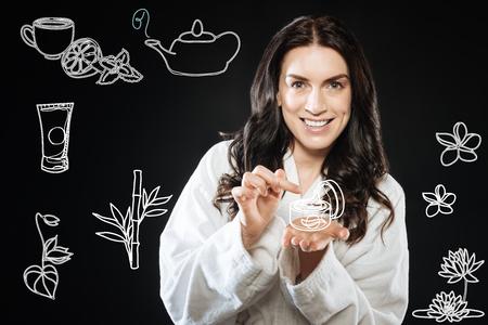 Schöne junge fröhliche Frau trägt einen Bademantel lächelnd und zufrieden , während sie ihre neue Gesichtsbehandlung zu Hause verwendet Standard-Bild - 98109946
