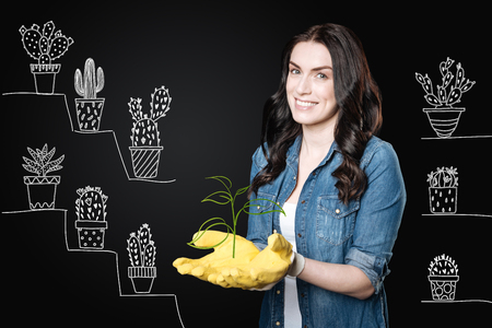 Cheerful emotional enthusiastic woman wearing yellow rubber gloves and smiling while working with her beautiful plants in the garden