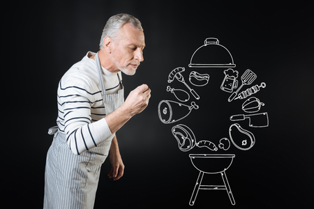 Relaxed calm experienced cook closing his eyes and smiling the dish while making a delicious supper Stock Photo