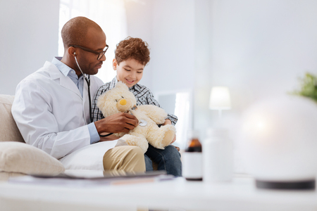 Plush patient. Appealing attractive male doctor sitting with boy while examining plush bear and talking Stock Photo