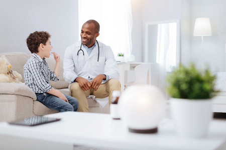 Private conversation. Satisfied merry male doctor and boy sitting on sofa while communicating and smiling