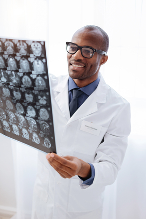 Brain structure. Glad cheerful male doctor wearing glasses and smiling and rising brain imaging Stock Photo
