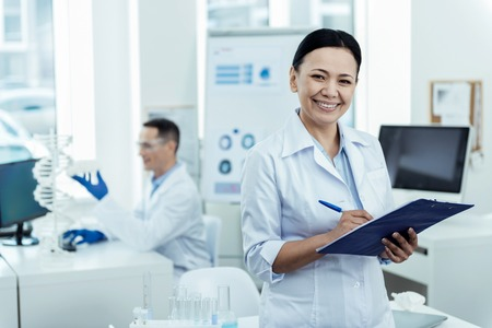 People of science. Pretty content dark-haired smart researcher smiling and wearing a uniform while taking notes and her colleague sitting in the background