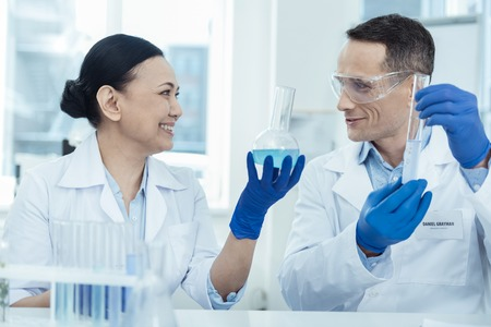 Great results. Cheerful intelligent experienced scientists smiling and wearing uniforms while making an experiment in the lab Stock Photo