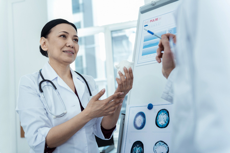 Mode of treatment. Pleasant asian doctor holding a model of heart while talking to her professional colleague