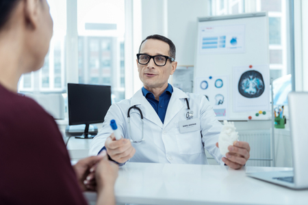 Medische wereld. Professionele arts aan de tafel zitten en praten met haar patiënt Stockfoto - 98189222