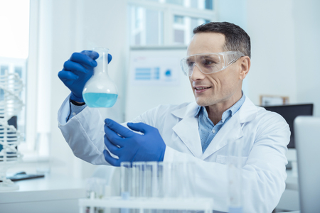 Important experiment. Pleasant handsome scientist working in a lab during an experiment