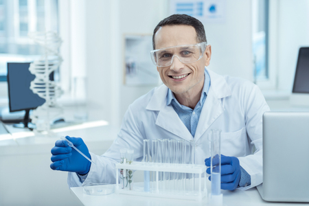 Applied bioengineering. Positive handsome professional bioengineer conducting a research while working in a lab Stock Photo