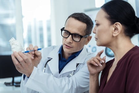 Have a nice check. Experienced doctor sitting with his patient while holding a model of heart Stock Photo