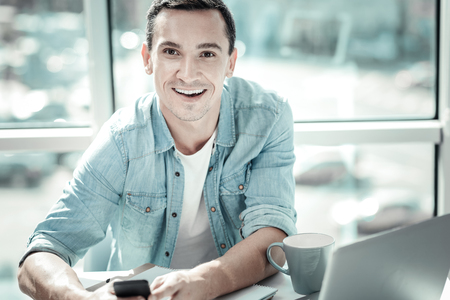 Work with pleasure. Satisfied gay pleasant man sitting by the table smiling and holding his cellphone.