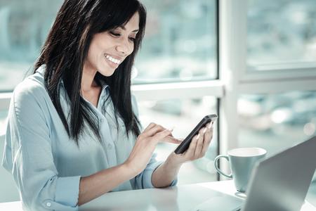 Neue Nachricht . Angenehme glückliche nette Frau , die im hellen Raum sitzt und ihr Mobiltelefon verwendet Standard-Bild - 98274694
