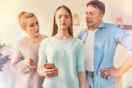 I am far from you. Teenager female keeping her eyes closed and holding telephone in right hand while standing between her parents
