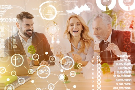 Funny idea. Optimistic emotional engineers sitting at the table and laughing while discussing funny unusual ideas connected with their common project Stock Photo