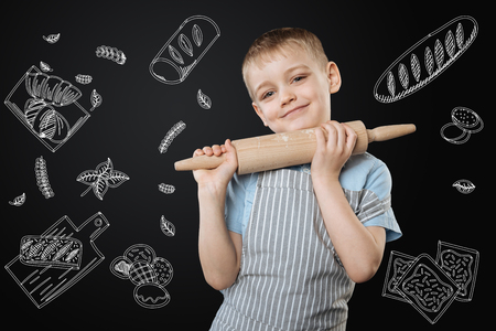 Smiling boy. Adorable positive little boy wearing an apron and holding a rolling pin while being in the kitchen Banco de Imagens