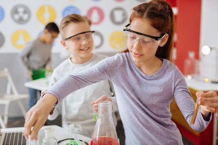 Best students. Diligent female teenage student in safety goggles mixing chemicals during chemistry class while her classmate watching her do so