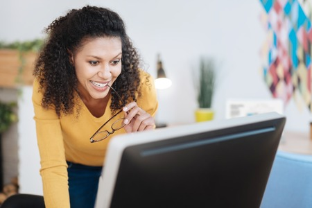 Delighted. Good-looking cheerful young curly-haired woman smiling and working on her laptop and holding her glasses Standard-Bild