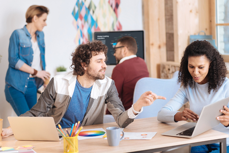 Amiable atmosphere. Good-looking inspired bearded man smiling and talking with his colleague about their work and their co-workers working in the background Stock Photo