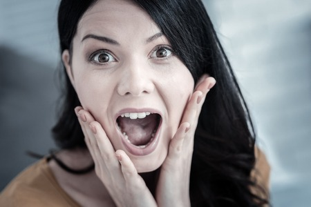 Expression of surprise. Portrait of a positive emotional young woman holding her cheeks and opening the mouth while expressing her surprise