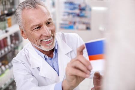 Pharmaceutical industry. Senior exuberant male pharmacist placing drug on shelf while grinning
