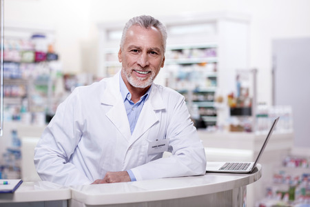 Ready for work. Senior exuberant male pharmacist staring at camera while leaning on stand