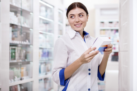 Interesting fact. Appealing female pharmacist staring aside while carrying medication