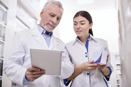 Experienced colleague. Low angle of reflective two pharmacists staring at tablet screen while standing on light background