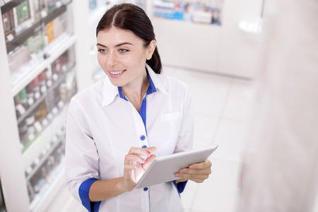 Electronic database. Top view of positive female pharmacist wearing uniform while using tablet Stock Photo