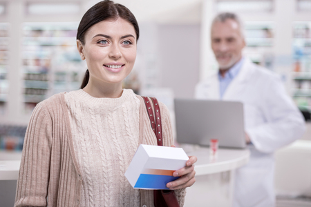 What I want. Joyful female client smiling while carrying drug
