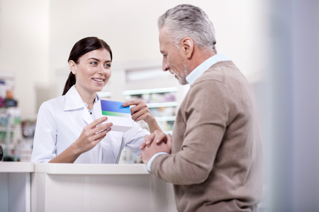 Organic components. Joyful female pharmacist showing mature man package while carrying medication Stock Photo