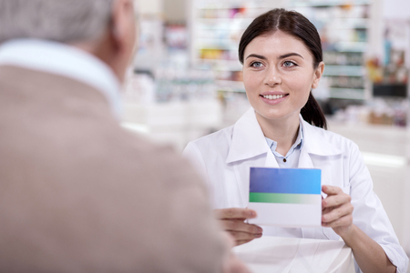 Side effects. Positive vigorous female pharmacist advising mature man about medicines while carrying medication