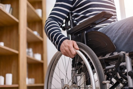 Way of movement. Handicapped man using his arms while operating his transport Stock Photo