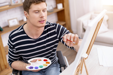 Concentrate on process. Handsome male person looking at canvas while sitting at his workplace