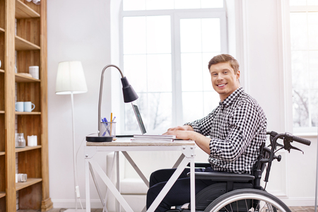 It is my cabinet. Joyful brunette invalid keeping smile on face while being on his wheelchair