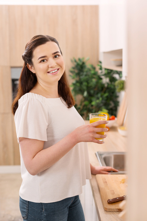 Start of day. Sincere ambitious woman grinning to camera while holding glass of orange juice