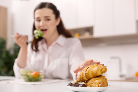 Harsh diet. Disturbed gloomy woman stretching for croissant while eating salad