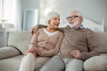 Elderly couple. Joyful aged man hugging his wife while sitting on the sofa