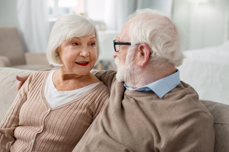 Aged couple. Nice pleasant man looking at his wife while sitting together with her on the sofa