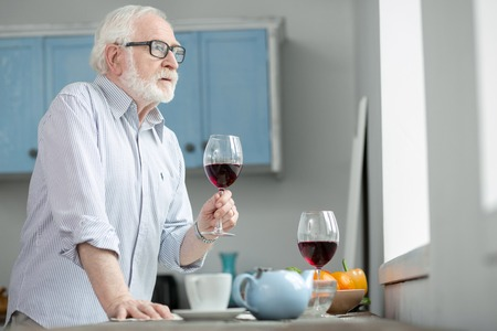 Lonely evening. Sad elderly man holding a glass of wine while looking into the window Banque d'images
