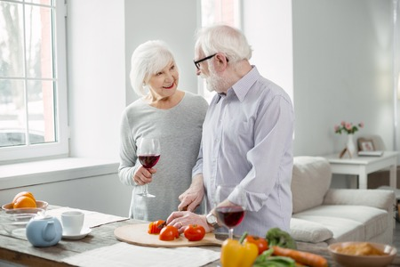Wonderful mood. Delighted aged people talking to each other while preparing dinner