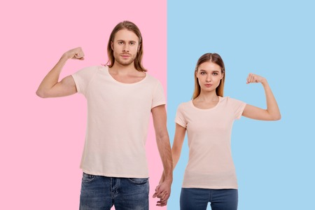 Stronger together. Pleasant young couple holding hands, intertwining their fingers, while raising arms and showing their biceps