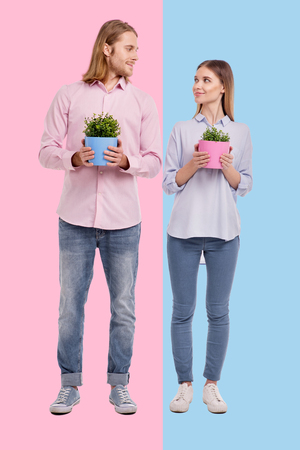 Love you. Joyful young couple looking at each other lovingly while posing with flower pots against a pink and blue backgrounds Stockfoto