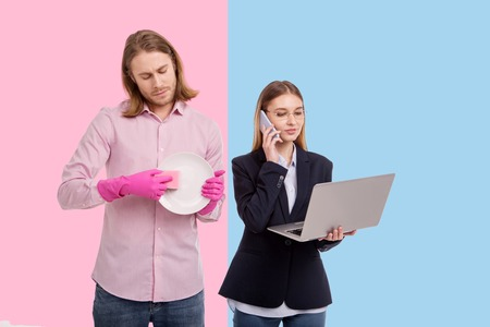 Switched gender roles. Pleasant young doing dishes while his girlfriend being an entrepreneur, working on a laptop and having a phone call with partners