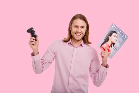 利用可能な異なる娯楽時間。ゲームコントローラと女性雑誌を持ち、ピンクの背景に孤立したポーズをとりながら微笑むピンクのシャツを着た魅力的な若者